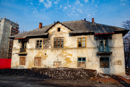 Old rotten abandoned house with boarded up windows, remnant of Soviet Voronezh