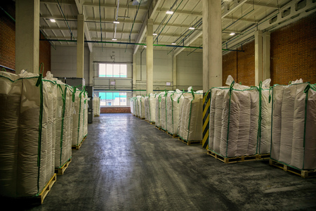 sinlight: Hangar warehouse with big white polyethylene bags of industrial and logistics companies. Warehousing on the floor Stock Photo