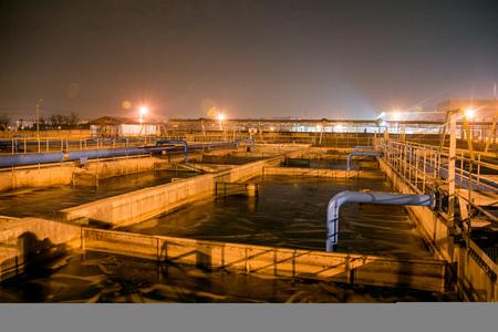 Moderna planta de tratamiento de aguas residuales de fábrica de productos químicos en la noche. Tanques de purificación de agua