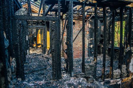 Interior de um apartamento queimado por fogo em um prédio de apartamentos. Feixes de madeira queimados Foto de archivo