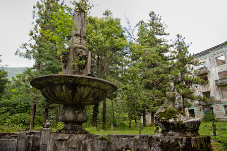 The abandoned miners ghost town Tquarchal (Tkvarcheli, Abkhazia). Idle fountain with lions head on the background of a ruined house.