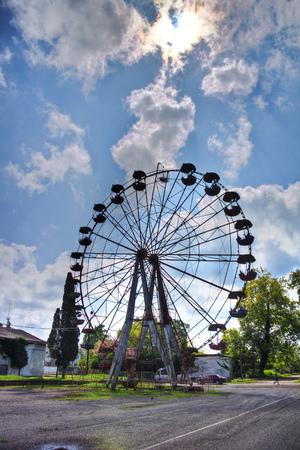 postwar: Old rusty abandoned Ferris wheel in the amusement park in Ochamchira, Abkhazia, Georgia