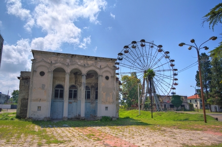 postwar: Abandoned House of Culture and old rusty abandoned Ferris wheel in the amusement park in Ochamchira, Abkhazia Stock Photo