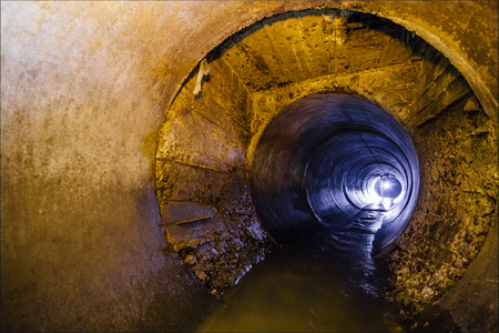 Dirty urban sewage flowing throw round sewer tunnel pipe
