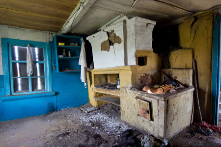 Interior of an abandoned Russian rural house, Russian stove.