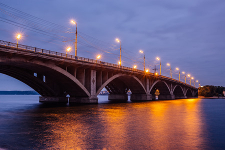 Beautiful illuminated Vogresovsky Bridge through Voronezh river at night