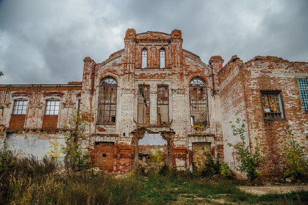 urban decay: Ruined facade of red brick industrial building in art nouveau style. Abandoned and destroyed sugar factory in Novopokrovka, Tambov region