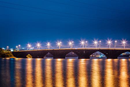 Beautiful illuminated Vogresovsky Bridge through Voronezh river at night.