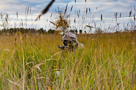 Man in gas mask and protective clothing holding rifle and hiding in high grass. Stalker and post-apocalyptic concept Stock Photo