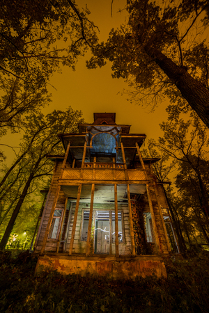 Old creepy wooden abandoned haunted mansion at night Stock Photo