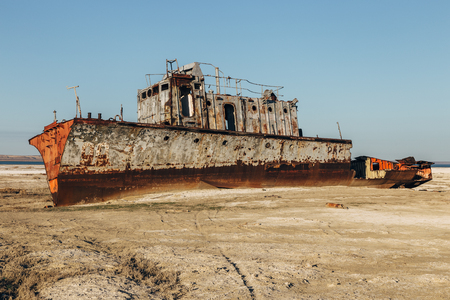 scrapyard: Aral sea disaster. Abandoned rusty fishing boat at the desert on the place of former Aral sea Stock Photo