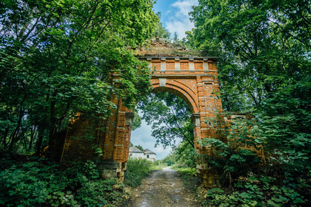 Abandoned and overgrown gateway of red brick to former Muromtsevs manor in Lipetsk region