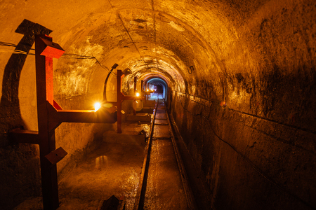 Abandoned round underground technical mine tunnel with a narrow-gauge railway Stock Photo