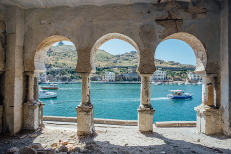 View to Balaklava bay through arched balcony in oriental style. Abandoned mansion on Black Sea coast Stock Photo