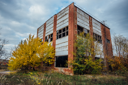 Old obsolete ruined concrete industrial building. Abandoned factory in autumn.  Concrete ruins in industrial district