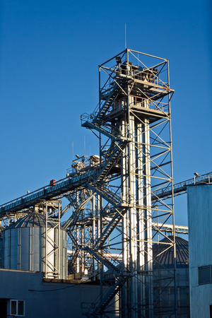 Tower of modern metal grain elevator with silos on blue sky background. Stock Photo