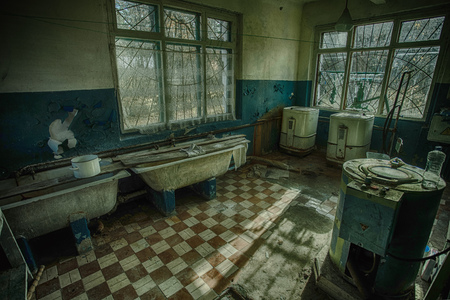 Sinister and creepy old laundry room with a dirty floor and broken wash machines and bathes in an abandoned psychiatric hospital.