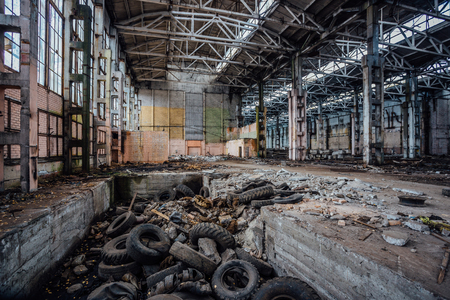 Junk of tires in abandoned industrial hall. Former Voronezh excavator factory.