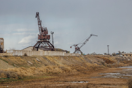 Consequences of Aral sea ecological catastrophe. Abandoned port with rusty cranes on the shore of dried Aral sea. Stock Photo