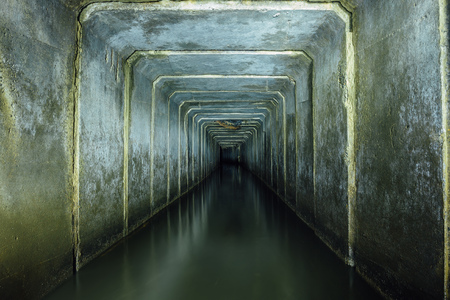 Dark and creepy flooded underground sewer concrete tunnel. Industrial wastewater and urban sewage flowing throw the tunnel.