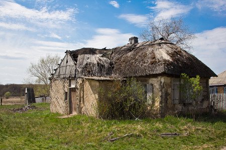 Abandoned Russian village. Ruins of rural house with thatched roof.