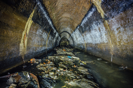 Flooded by dirty industrial wastewater sewage collector. Sewer tunnel under city Voronezh full of garbage. Stock Photo