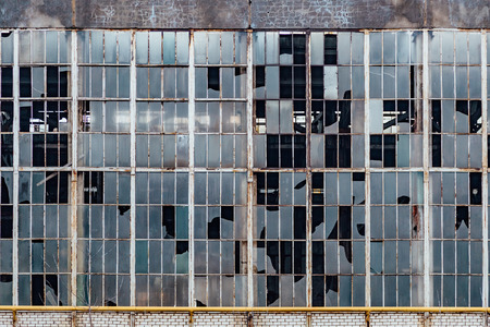 Broken windows in an old abandoned industrial building.