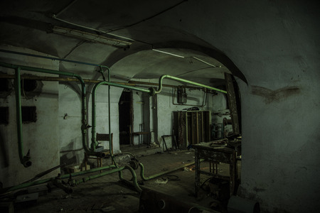 Old creepy cellar of abandoned asylum. Old rotten boiler, heating pipes. Banque d'images