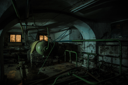 Old creepy cellar of abandoned asylum. Old rotten boiler, heating pipes. Stok Fotoğraf