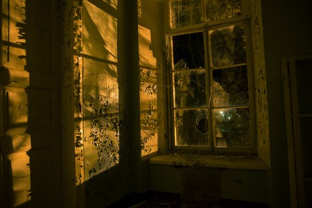 Night, broken window, peeled paint, abandoned building. Stock Photo
