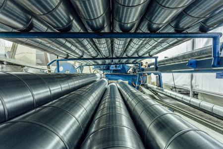 Cylindrical steel pipes. Round metal tubes in metalworking workshop. Stock Photo