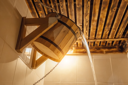 Wooden bucket for Russian bath or sauna. Cold water pours from bucket in the steam room. Banque d'images