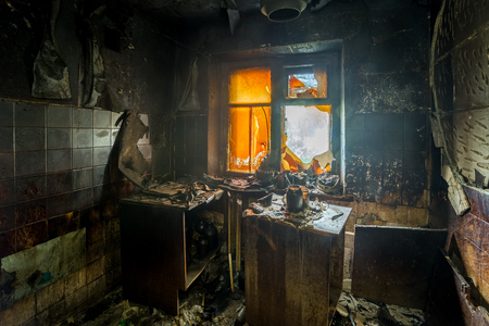 Burnt apartment house interior. Burned furniture and charred walls in black soot.