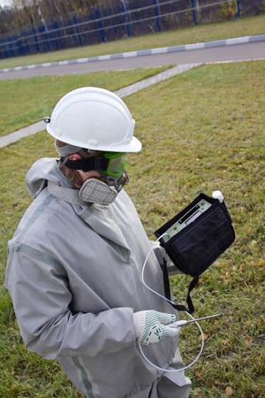 Worker in chemical protection suite are measuring the concentration of toxic gases with a gas analyzer in the infected area.