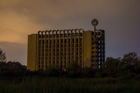 Ruined Abandoned multi-story building at night. Abandoned sanatorium in Eshera, Abkhazia, Georgia. Stock Photo