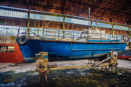 Old rusty boats in hangar in repair factory.