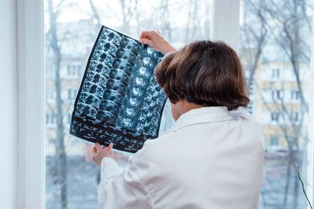 El doctor en bata blanca examina los resultados de la resonancia magnética (RMN) de la articulación de la cadera femenina. Foto de archivo