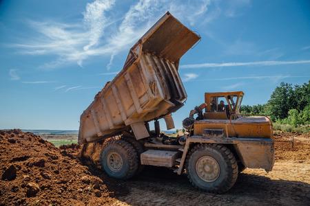 Dump truck unloads soil with crashed stone. Foto de archivo