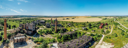 Aerial panoramic view of abandoned industrial area at rural landscape, concrete buildings, industry and agricultural district.