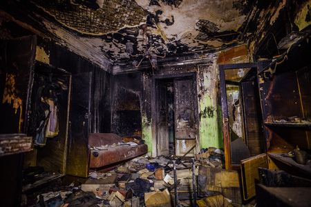 Burnt mansion. Burned furniture, door, charred walls and ceiling.