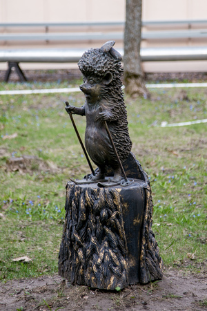 Funny decorative statue of a hedgehog on skis on a stump in the park. Stockfoto