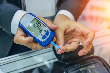 Man measuring glucose level in blood by using digital glucometer. Banque d'images