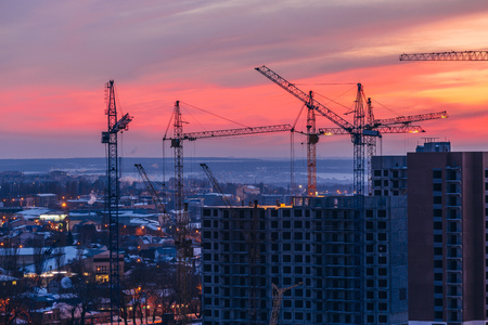 Cranes and high-rise buildings construction site on crimson sunset sky background. Voronezh, Russia. Stock Photo