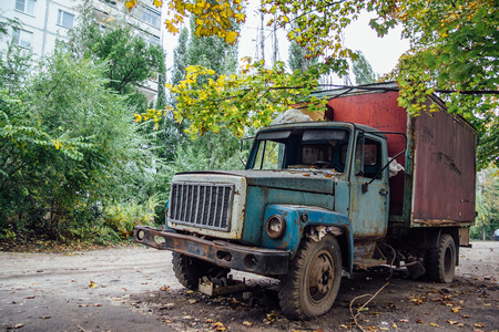 Old rusty truck with broken windows at abandoned overgrown part of town. Stock Photo