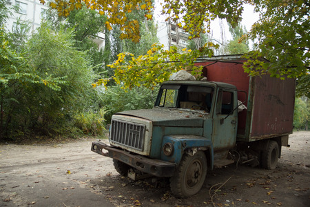 Old rusty truck with broken windows at abandoned overgrown part of town. Banco de Imagens