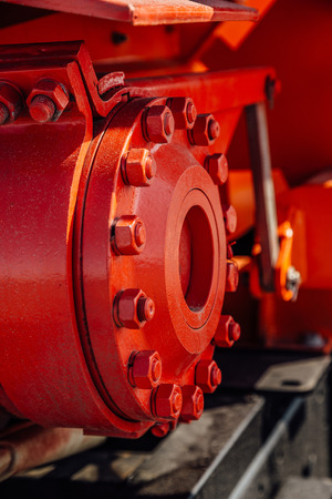Machine part. Joint of flanges by bolts and nuts red colored. Close-up view. Selective focus