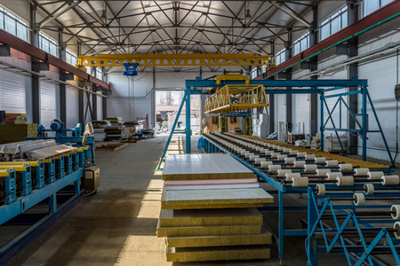 Thermal insulation sandwich panel production line. Machine tools, roller conveyor and gantry crane in workshop.