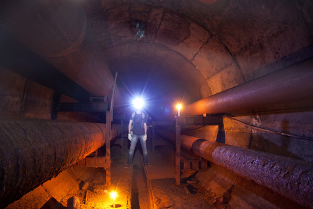 Urban explorer with candle in underground communication, heating main, sewer tunnel, etc.