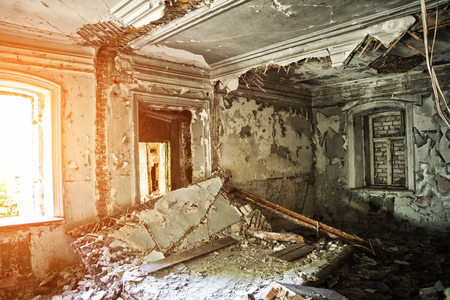 Old ruined abandoned mansion interior. Collapsed ceiling, peeled walls