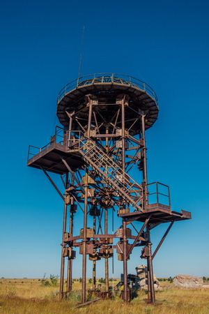 Old rusty iron abandoned watch tower in wastelands Archivio Fotografico